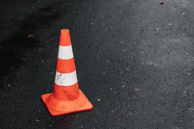 Stożek drogowy, z biało-pomarańczowymi paskami na szarym asfalcie