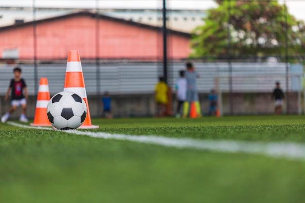 Stożek taktyki piłki nożnej na boisku z tłem treningowym trening dzieci w piłce nożnej