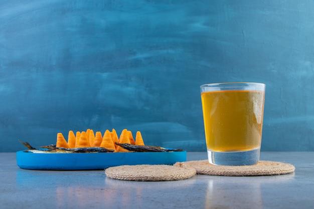 Stożkowe chipsy i suszona ryba na drewnianym talerzu obok szklanki piwa na podstawce, na marmurowym tle.