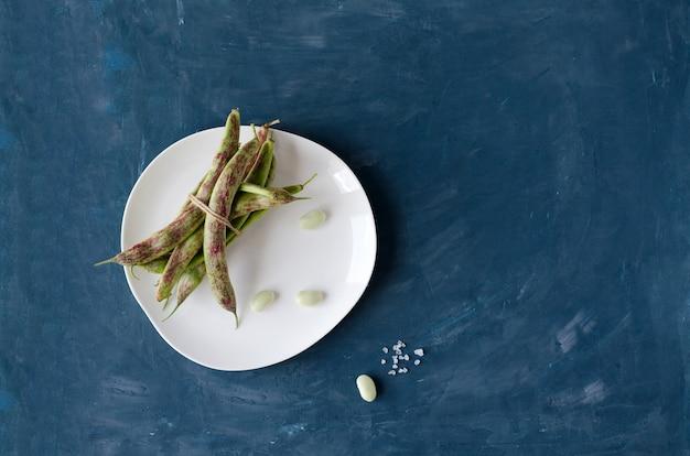 Strąki fasoli szparagowej związane jutą leżą na białym talerzu i niebieskim