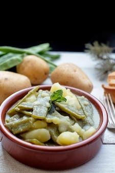 Strąki z ziemniakami w glinianym garnku wraz ze składnikami na białym rustykalnym drewnianym stole