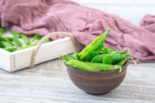 Strąki zielonego groszku na zewnątrz w małej misce na drewnianym stole