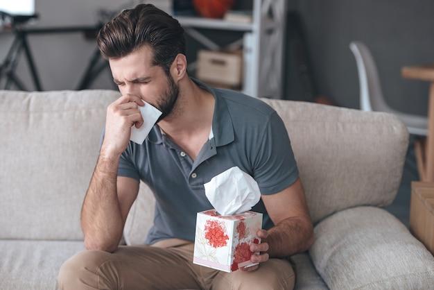 Straszna alergia. sfrustrowany przystojny młody mężczyzna kicha i używa chusteczek siedząc na kanapie w domu