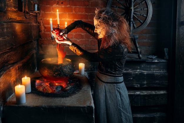 Straszna czarownica gotująca zupę z częściami ludzkiego ciała, mroczne moce czarów, duchowy seans ze świecami.