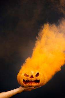 Straszna dynia halloweenowa z pomarańczowym dymem