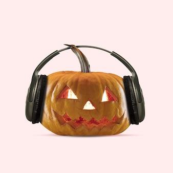 Straszna dynia na koralowym tle, noc strachu. nowoczesny design ze słuchawkami. halloween, czarny piątek, cyber poniedziałek, sprzedaż, koncepcja jesień. ulotka reklamowa. kolaż sztuki współczesnej.