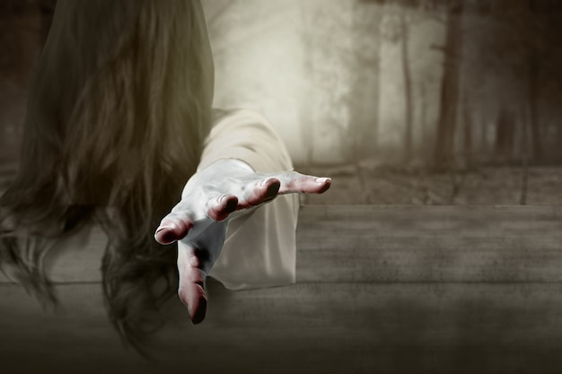 Straszna kobieta-duch stojąca z nawiedzonym lasem