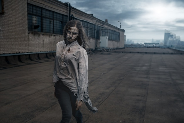 Straszna kobieta zombie na dachu opuszczonego budynku, śmiertelny pościg. horror w mieście, przerażający atak pełzających, apokalipsa