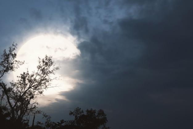 Straszna nocna scena z księżycem i ciemnymi chmurami
