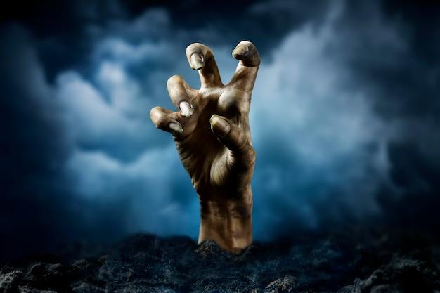 Straszna ręka zombie z ziemi w nocy