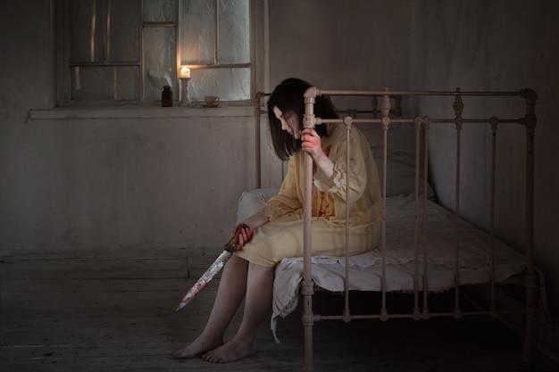Straszna szalona dziewczyna pokryta krwią z nożem w zamkniętym pokoju w nocy