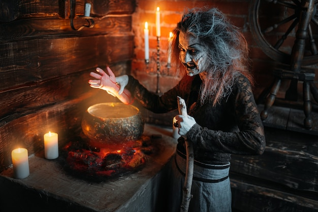 Straszna wiedźma czyta zaklęcie nad garnkiem, seans