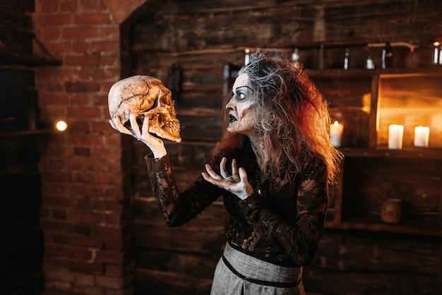 Straszna wiedźma czyta zaklęcie, rytuał z ludzką czaszką, mroczne moce czarów, seans duchowy.