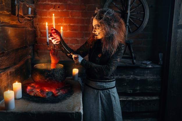 Straszna wiedźma gotująca zupę z częściami ludzkiego ciała