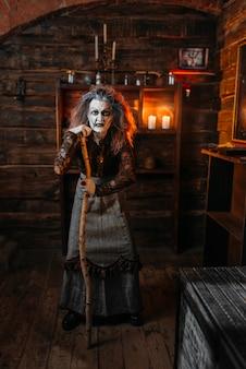 Straszna wiedźma stoi oparta na lasce, seans