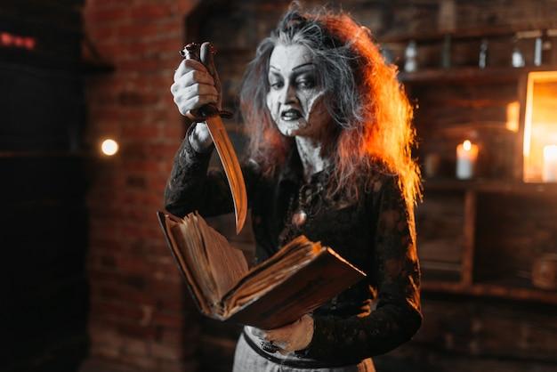 Straszna wiedźma trzyma księgę zaklęć i nóż