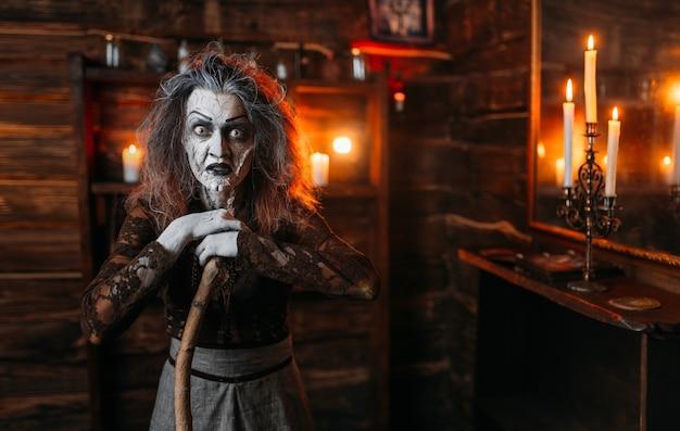 Straszna wiedźma z laską przy lustrze i świecami