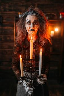 Straszna wiedźma ze świecznikiem i laską czyta zaklęcie