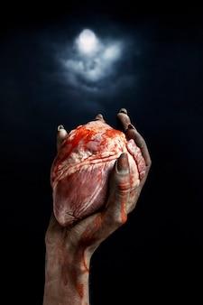Straszna żeńska ręka zombie trzymająca serce