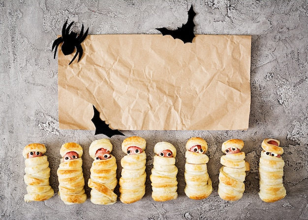 Straszne kiełbasy mumie w cieście z śmiesznymi oczami na stole. dekoracja makieta.