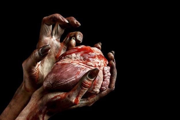 Straszne kobiece ręce zombie trzymające serce