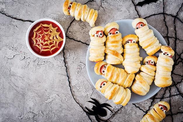 Straszne mumie kiełbasowe w cieście o śmiesznych oczach na stole. zabawna dekoracja. halloweenowe jedzenie. widok z góry. leżał płasko