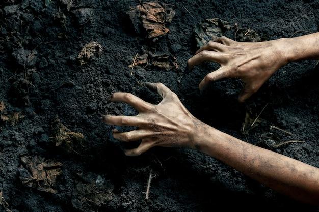 Straszne ręce zombie na ziemi