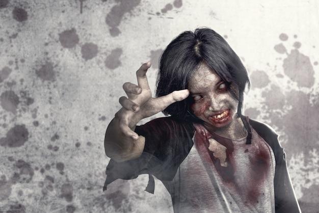 Straszne zombie z krwią i raną na ciele chodzące po miejskiej ulicy