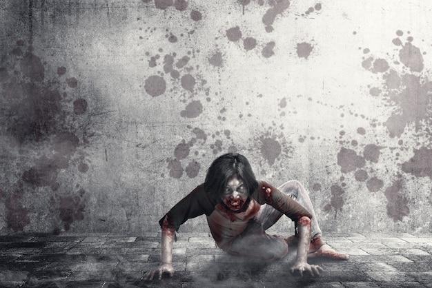 Straszne zombie z krwią i raną na ciele pełzające po miejskiej ulicy