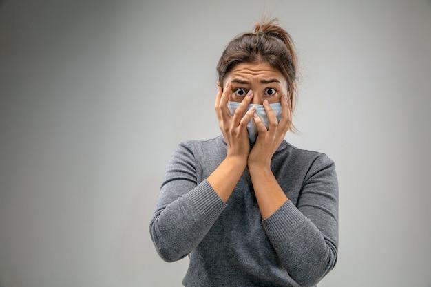 Straszne życie. kaukaska kobieta nosząca maskę oddechową chroniącą przed zanieczyszczeniem powietrza i cząsteczkami kurzu przekracza granice bezpieczeństwa. pojęcie opieki zdrowotnej, ochrony środowiska, ekologii. alergia, ból głowy.
