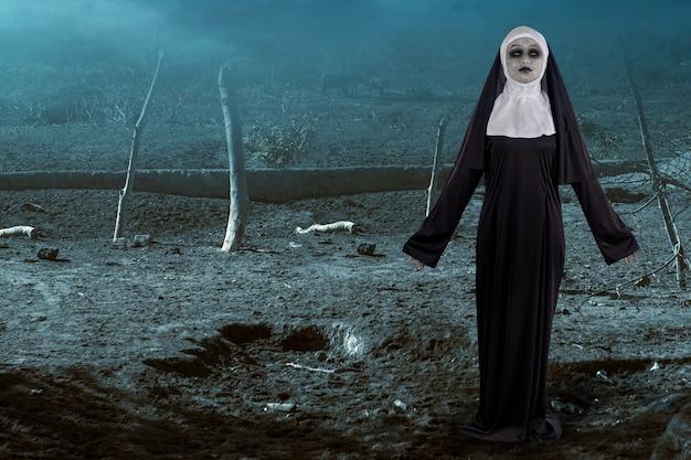 Straszny diabeł zakonnica stojąca na tle nocnej sceny