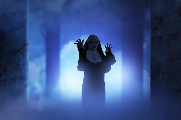 Straszny diabeł zakonnica stojąca w opuszczonym budynku. koncepcja halloween