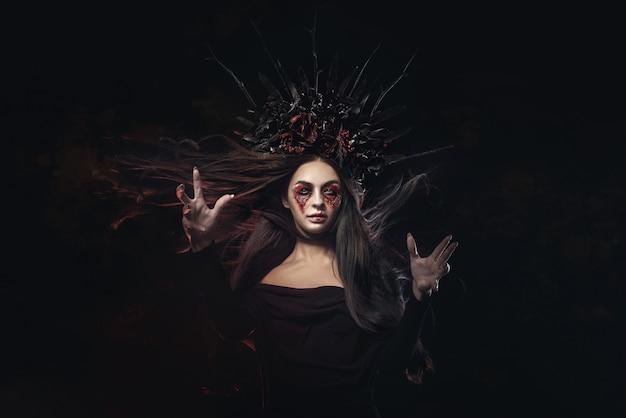 Straszny horror portret kobiety wampirów halloween. piękno wampira czarownica dama z krwią na ustach pozowanie w głębokim lesie. projektowanie mody. trzyma świecę w dłoniach i czyta przekleństwa