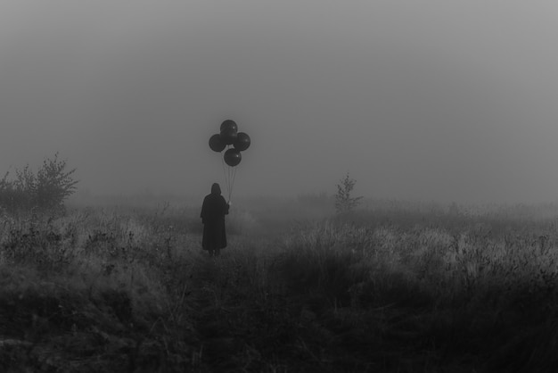Straszny mężczyzna w pelerynie z kapturem i balonami w ręku stoi na zamglonym polu. mroczna koncepcja mistycznych koszmarów