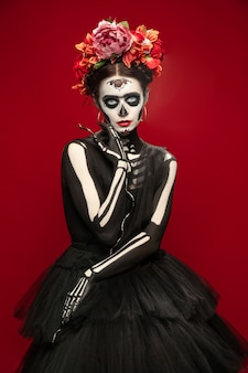 Straszny. młoda dziewczyna jak śmierć santa muerte saint lub sugar skull z jasnym makijażem. portret na białym tle na czerwonym tle studio z copyspace. świętowanie halloween lub dnia zmarłych.