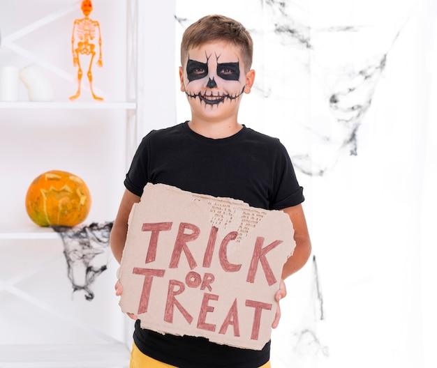 Straszny młody chłopak trzyma znak cukierek albo psikus