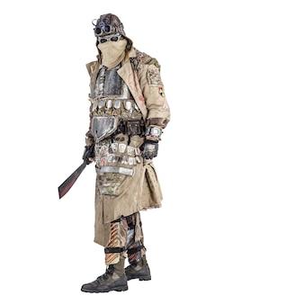 Straszny postapokaliptyczny ocalały w ręcznie robionych pancernych ubraniach, uzbrojony w maczetę, niebezpieczny stwór z twarzą ukrytą za maską i okularami, w szmatach, stojący z zimną bronią w ręku