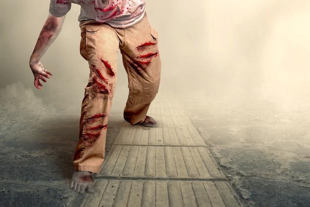 Straszny zombie z krwią i raną na ciele chodzącym na mglistym tle