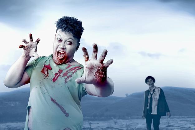 Straszny zombie z krwią i raną na ciele chodzącym po polu