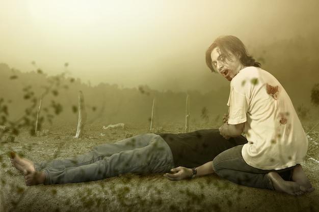 Straszny zombie z krwią i raną na ciele pożerający martwego mężczyznę na polu