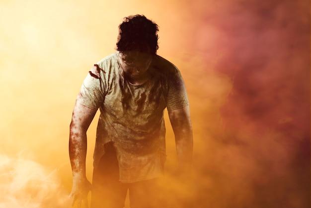 Straszny zombie z krwią i raną na ciele stojący na dramatycznym tle