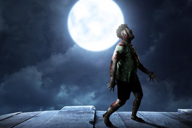 Straszny zombie z krwią i raną na ciele stojący na tle nocnej sceny