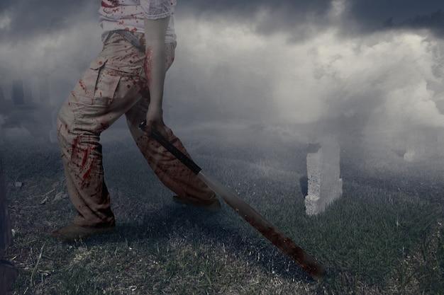 Straszny zombie z krwią i raną na ciele trzymający kij bejsbolowy stojący na cmentarzu