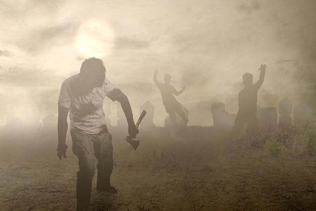 Straszny zombie z krwią i raną na ciele trzymający siekierę idący po cmentarzu