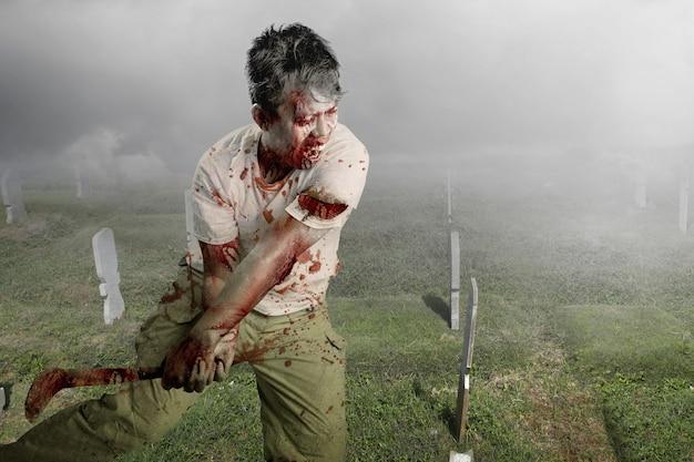 Straszny zombie z krwią i raną na ciele trzymający sierp stojący na cmentarzu