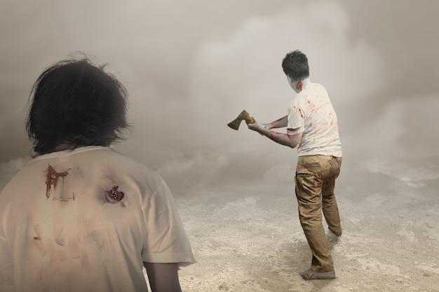 Straszny zombie z krwią i raną na ciele trzymający topór stojący na mglistym tle