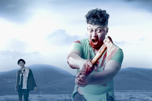 Straszny zombie z krwią i raną na ciele trzymający topór stojący na polu