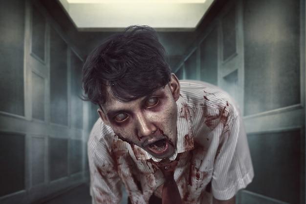 Straszny zombie z zakrwawioną twarzą w ciemnym miejscu