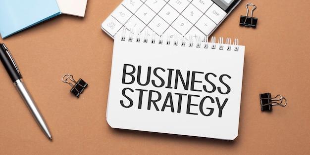 Strategia biznesowa na notatniku z długopisem, okularami i kalkulatorem