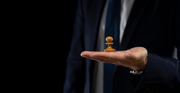 Strategia i koncepcja planowania biznesowego. biznesmen w ciemnym garniturze trzyma białego pionka szachowego na łuskowatym tle. strategia i taktyka.
